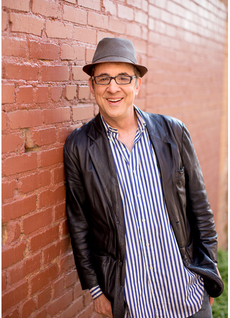 Ari Ross in a leather jacket hat and striped shirt shoulder against a brick wall