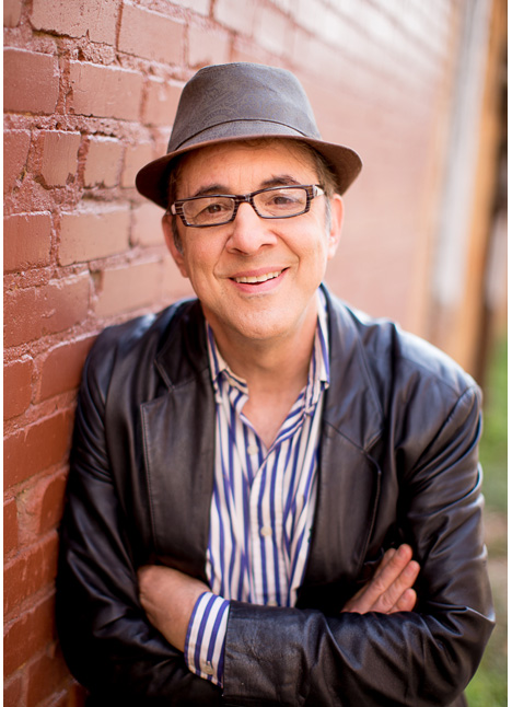 Ari Ross in a leather jacket hat and striped shirt with arms folded leaning against a brick wall